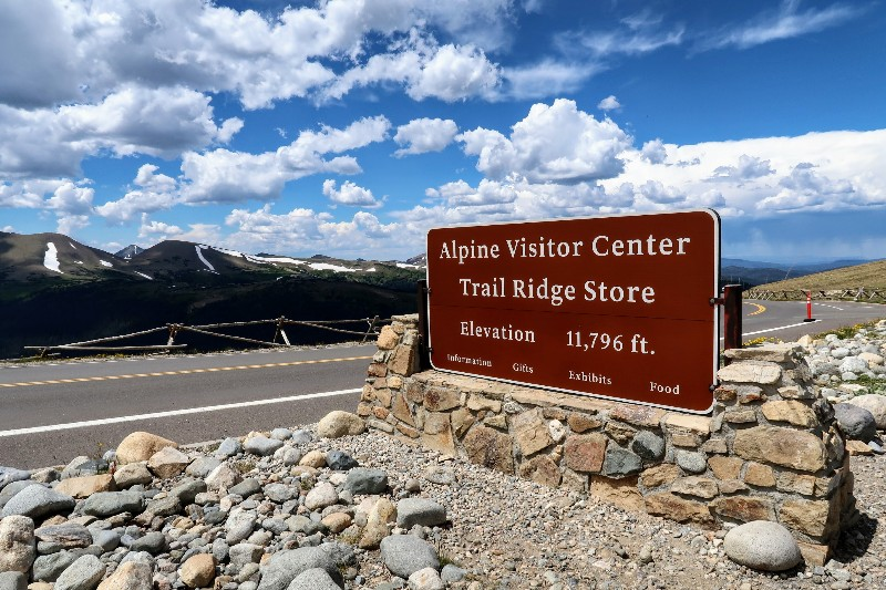 Alpine Visitor Center sign with mountains in the background