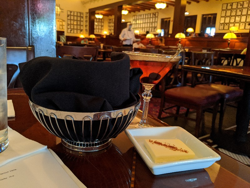 A cocktail and bread basket on table of Hollywood Brown Derby at Hollywood Studios.