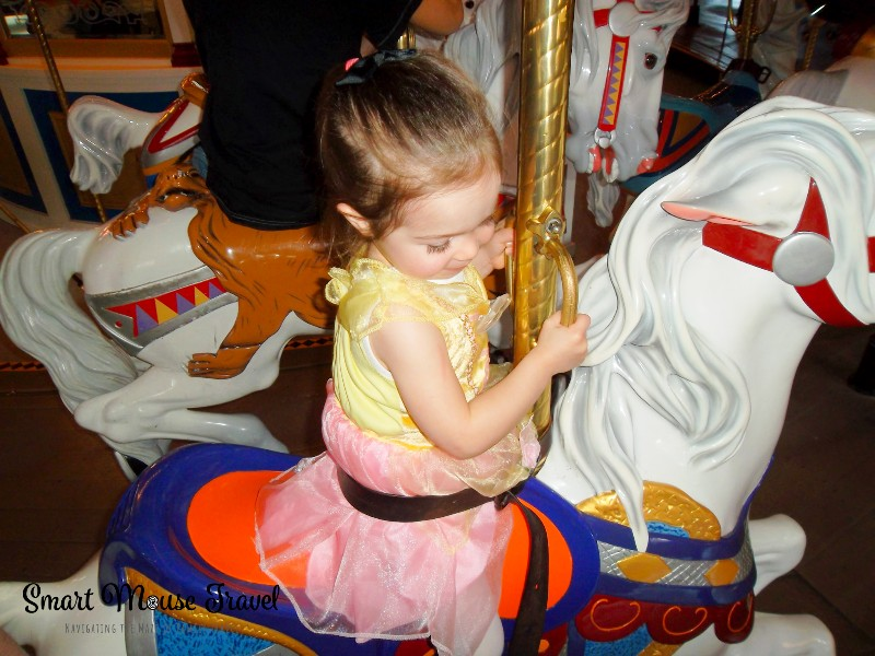 Toddler riding Prince Charming Regal Carrousel at Magic Kingdom.