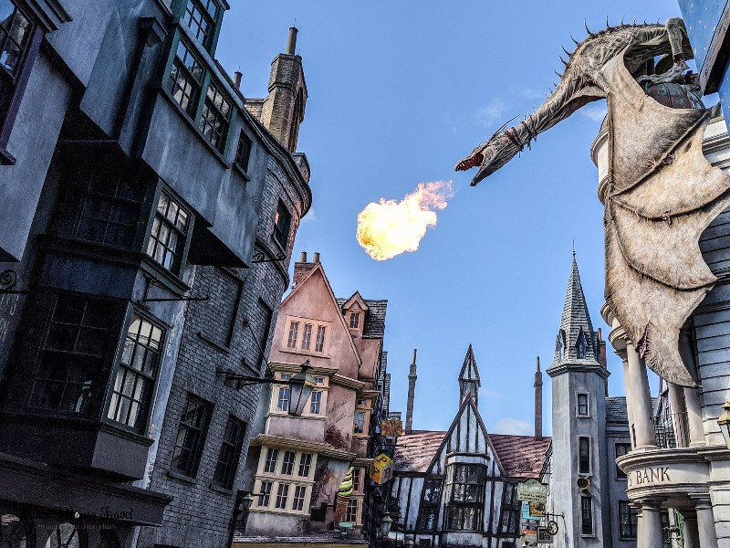 Dragon breathing fire over Diagon Alley. Although still magical, the Wizarding World of Harry Potter during COVID has several changes that you need to know when planning your trip.