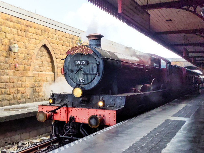 Hogwarts Express train arriving in Hogsmeade station. Although still magical, the Wizarding World of Harry Potter during COVID has several changes that you need to know when planning your trip.