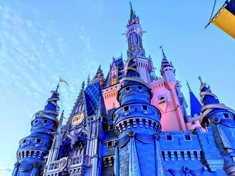 Night time view of Cinderella's Castle at Magic Kingdom. Is it worth it to stay at a Disney World resort? Here's what you should consider before booking a stay off-site for Disney World.