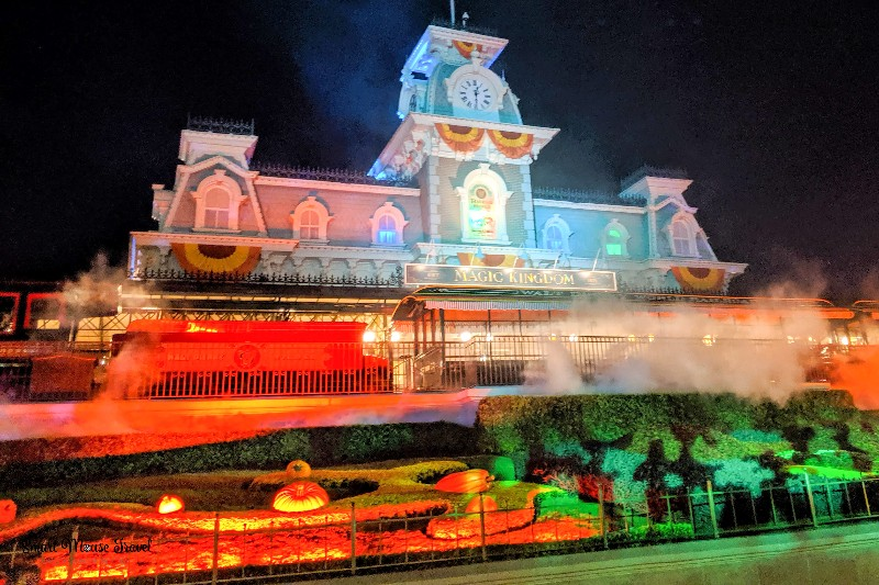 Magic Kingdom train station with orange and green uplights and fog for Halloween. Disney After Hours Magic Kingdom Boo Bash is a new way to celebrate Halloween at Disney, but is this special ticket event worth it?