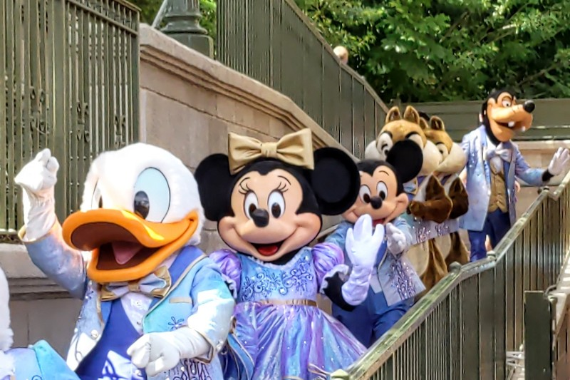 Donald, Minnie, Mickey and more exit Main Street train station dressed in their sparkly EARidescent costumes