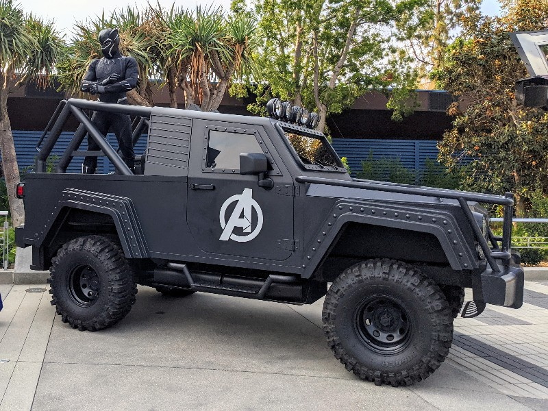 Black Panther perched on back of Avengers vehicle.