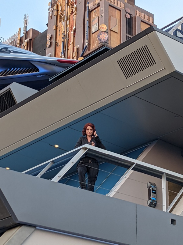 Black Widow waving to guests from Avengers Headquarters at Disney California Adventure.