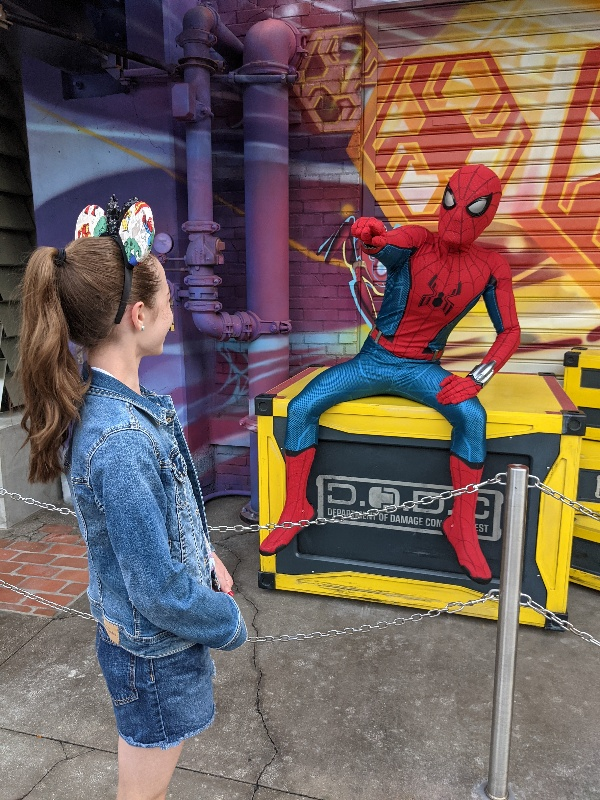 Girl chats with Spider-Man in Avengers Campus.