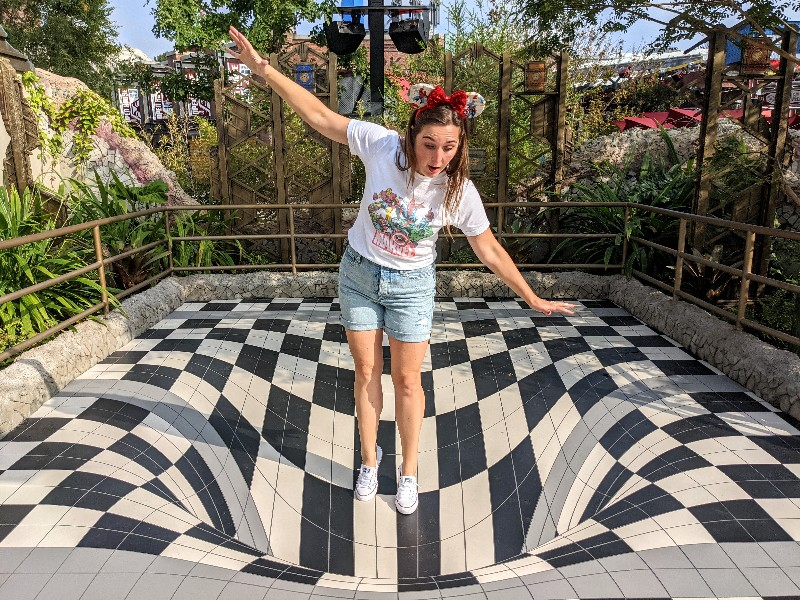 Woman pretends to fall in hole at Avengers Campus in a fun photo op. Avengers Campus seamlessly integrates Marvel characters, cool styling, and unique Avengers Campus rides into your Disneyland vacation.