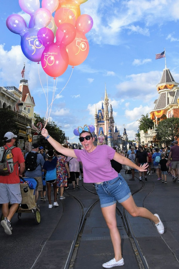 Woman pretends to float away with Mickey balloons at Magic Kingdom