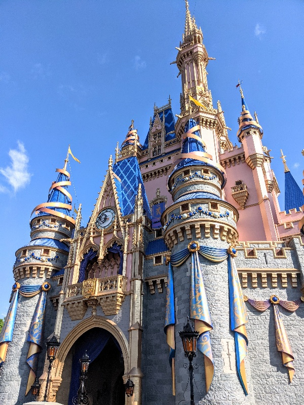 Up close view of Cinderella's Castle with gold ribbons adorning turrets, jewels, and gold and blue filigree bunting.