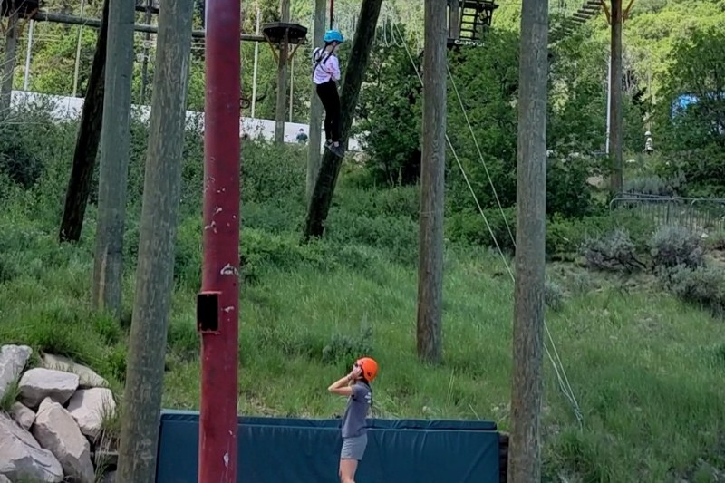 Girl descends from 65 foot high platform on a harness.