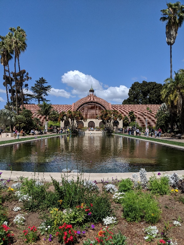 Balboa Park botanical building framed by blue skies above and a lily pond in front.
