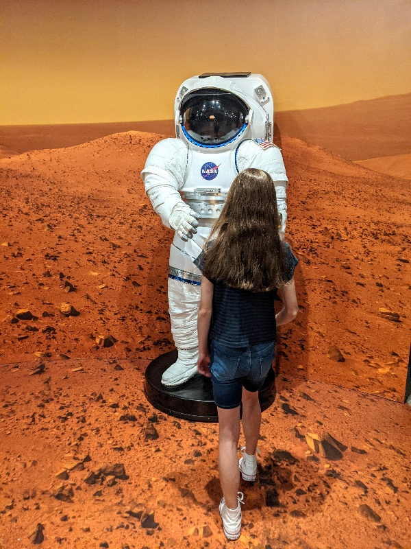 Girl approaches NASA astronaut suit at San Diego Air and Space Museum