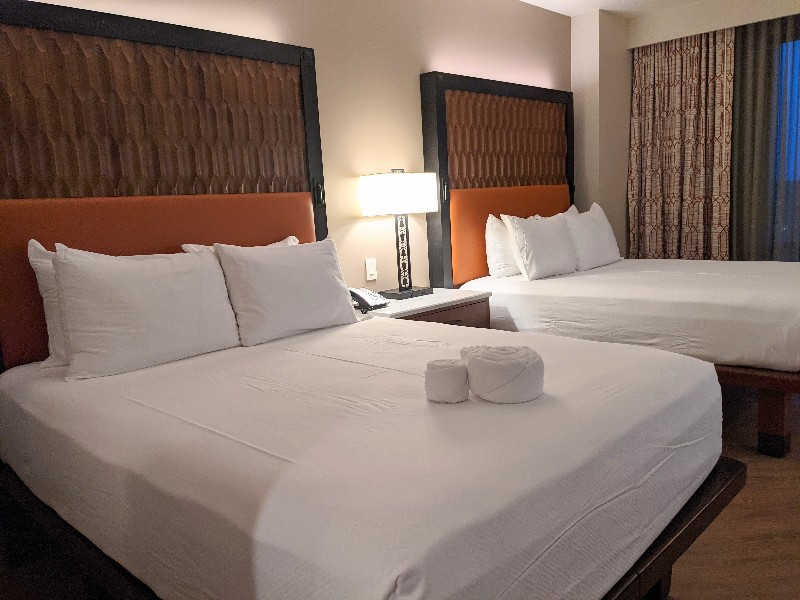 Two queen beds have wood-like headboards with a pop of orange and crisp white sheets at Gran Destino Tower.