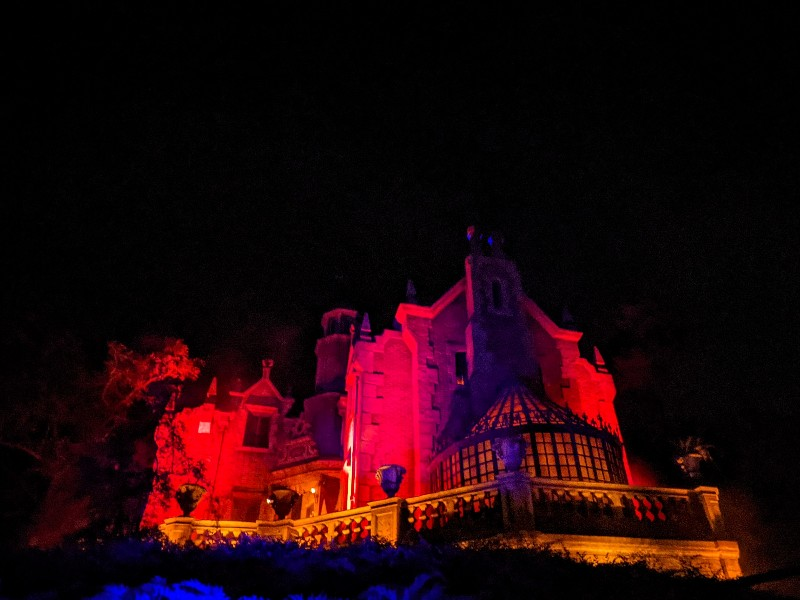 Haunted Mansion lit in reds and orange lighting during Disney After Hours Boo Bash.