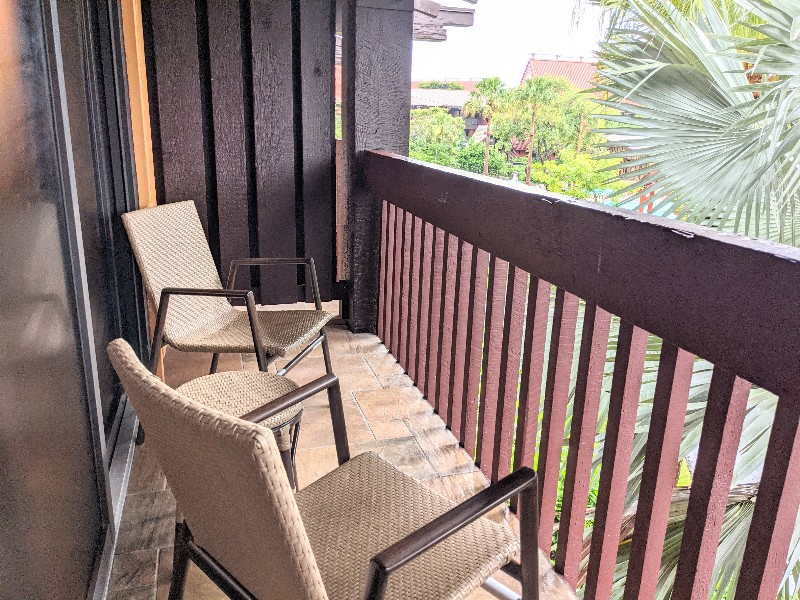 Two chairs on a private balcony surrounded by a palm tree.
