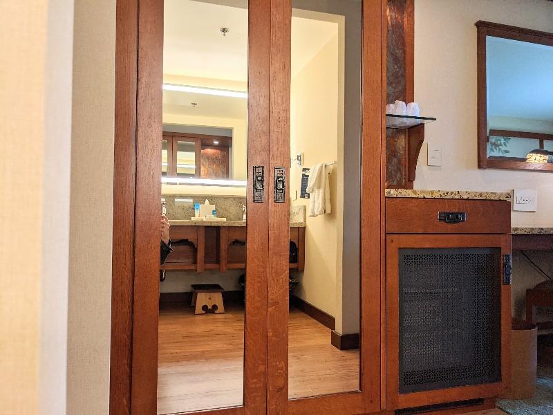 Double mirrored closet doors reflect the double vanity at Disney's Grand Californian standard room bathroom.