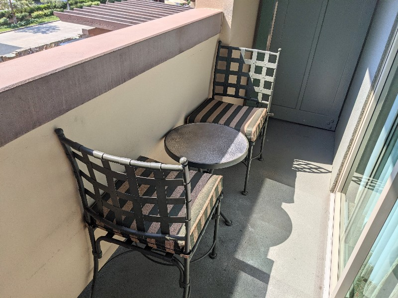 Two outdoor chairs plus a side table on a small balcony.