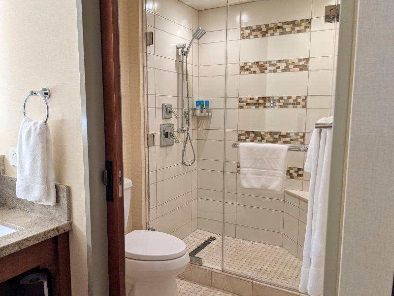 Tiled stand up shower with both rainhead and handheld shower head options.