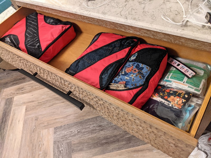 Large drawer open with several packing cubes inside.