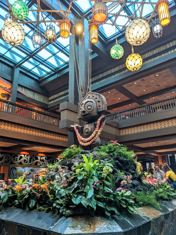 Carved wood figure surrounded by hanging lanterns and lush plants in the Polynesian Resort lobby.