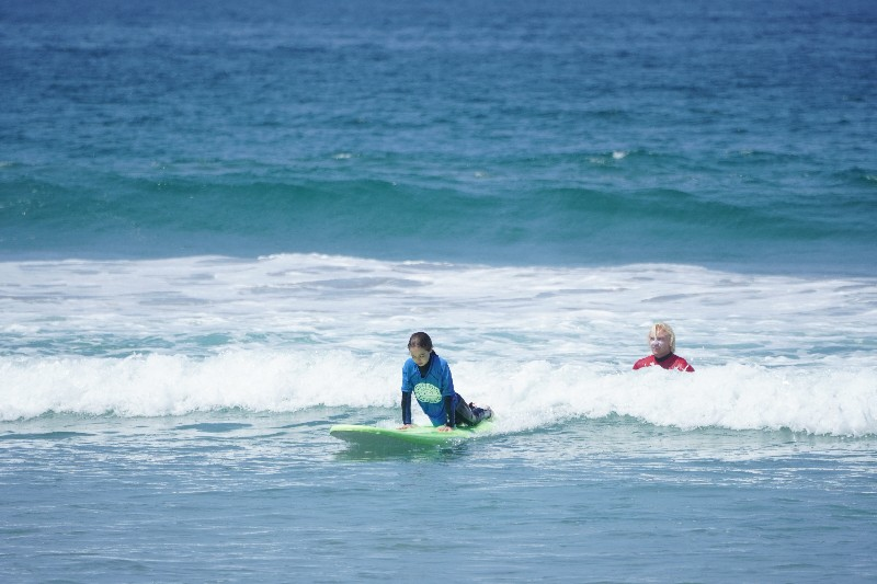 Girl prepares to stand on surf board while Pacific Surf School instructor looks on