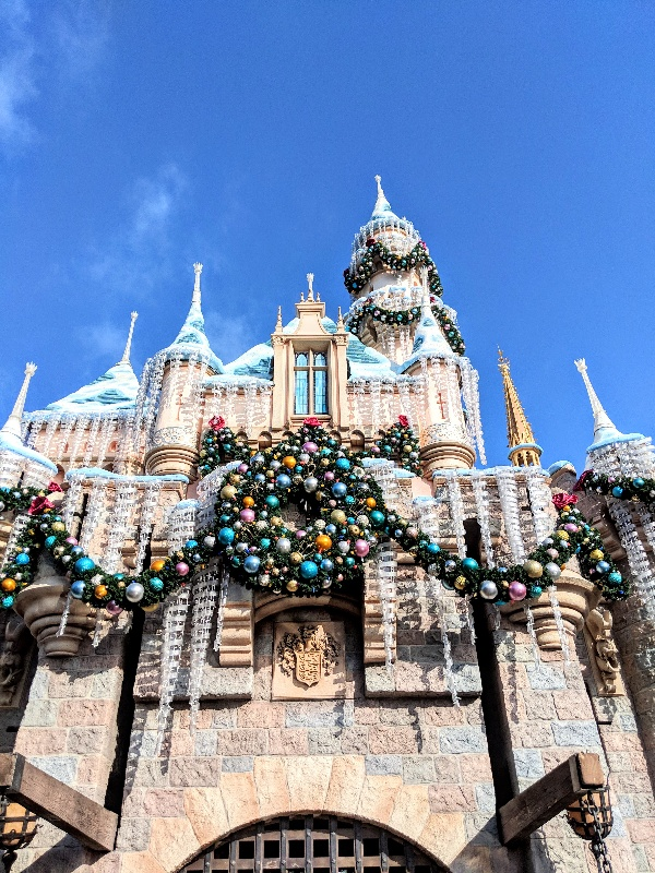 Close up view of Sleeping Beauty Castle adorned in garland, icicles, colorful ornaments, and snow capped turrets at Disneyland