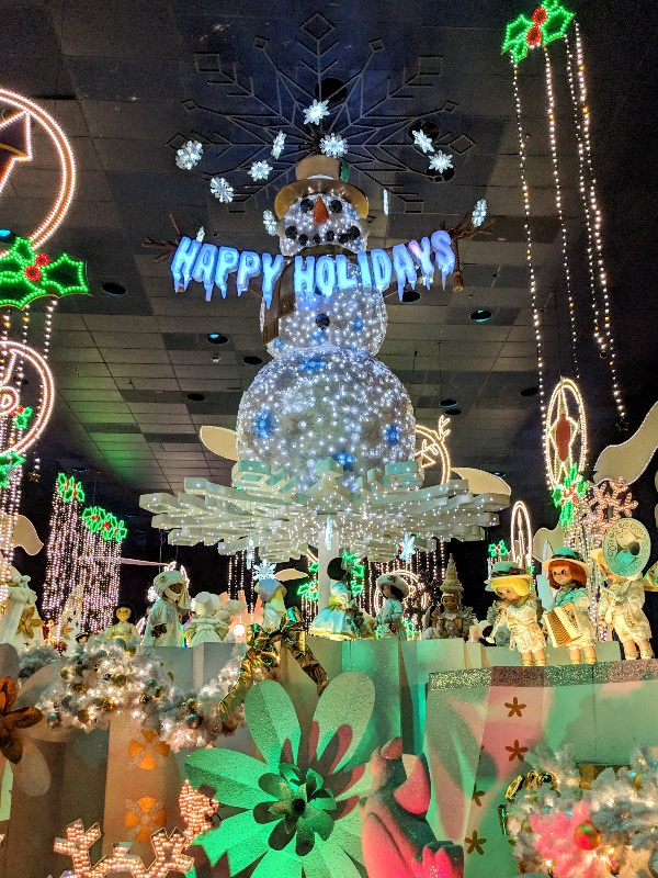"""A large light up snowman holds a Happy Holiday sign while red and green lights accent """"it's a small world"""" holiday decor at Disneyland"""