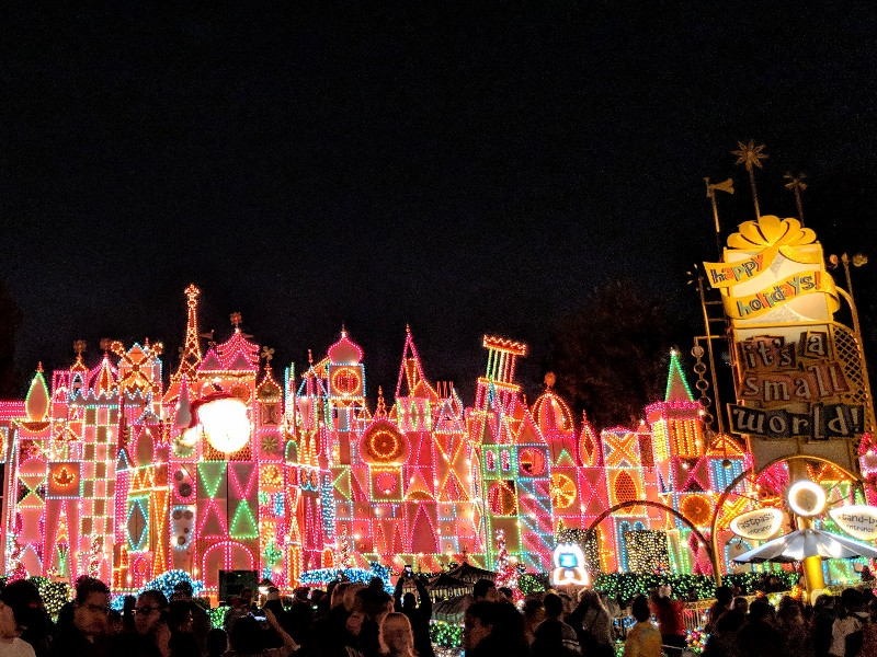 """Thousands of colorful lights shine in the darkness on the facade of """"it's a small world"""" Holiday"""