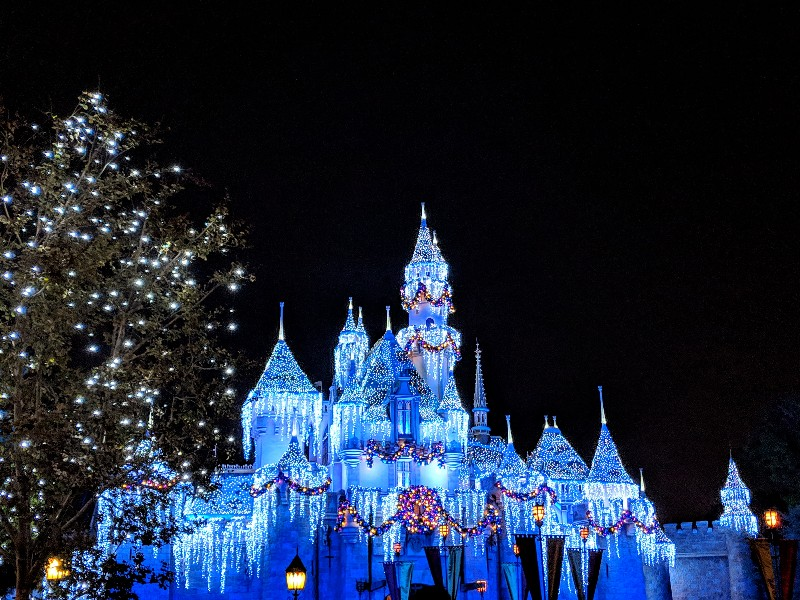 Icy blue lights and icicles make Sleeping Beauty Castle even more stunning at night during Disneyland Christmas season