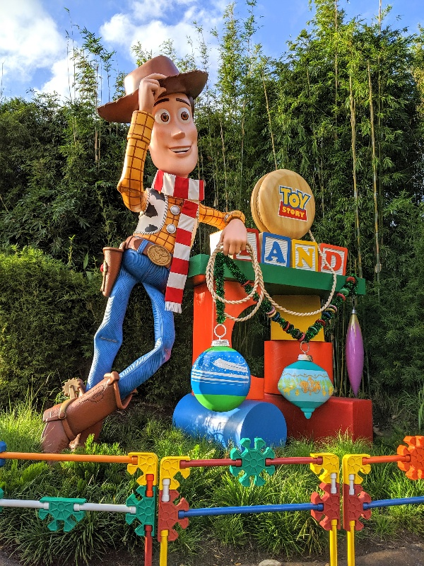 Woody in a striped scarf and ornaments hanging from the Toy Story Land sign during Disney World Christmas