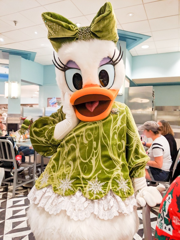 Daisy Duck in a peridot velvet top, matching bow, and stunning accesories at Minnie's Seasonal Dine
