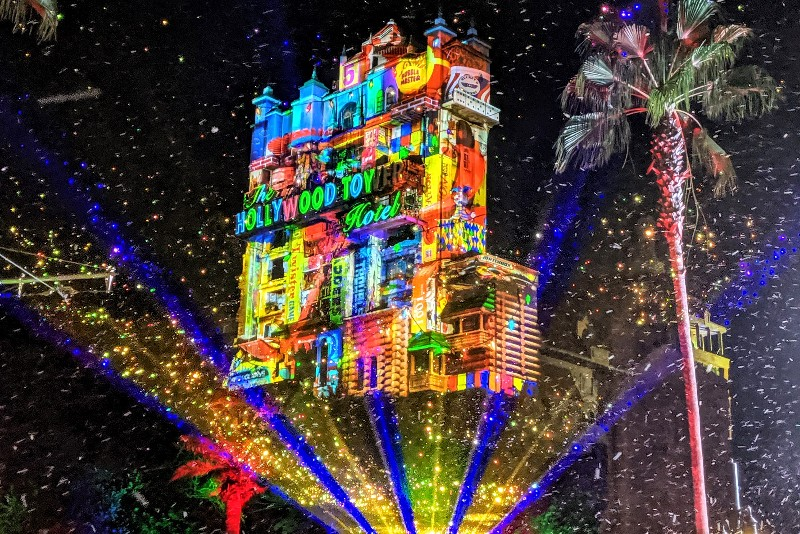 Faux snow falls in Hollywood Studios with Sunset Seasons Greetings projections on the Tower of Terror during Disney World Christmas