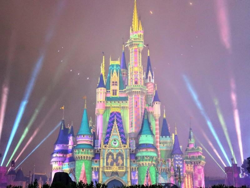 Pastel lights make Cinderella Castle look like a treat during Minnie's Wonderful Christmastime Fireworks at Magic Kingdom