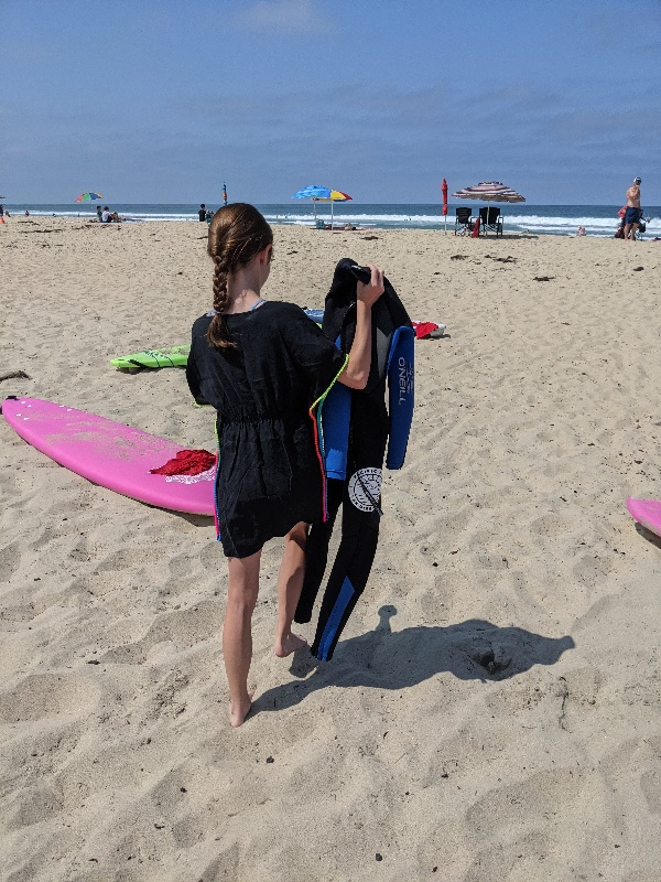 Girl holds wetsuit as she prepares for Pacific Surf School lesson