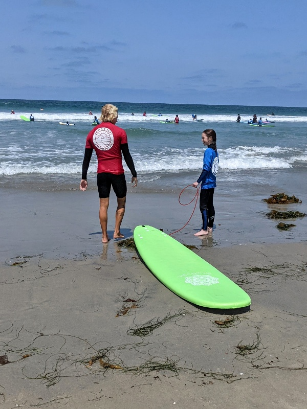 Surf instructor and student take a quick break and discuss technique at Pacific Beach