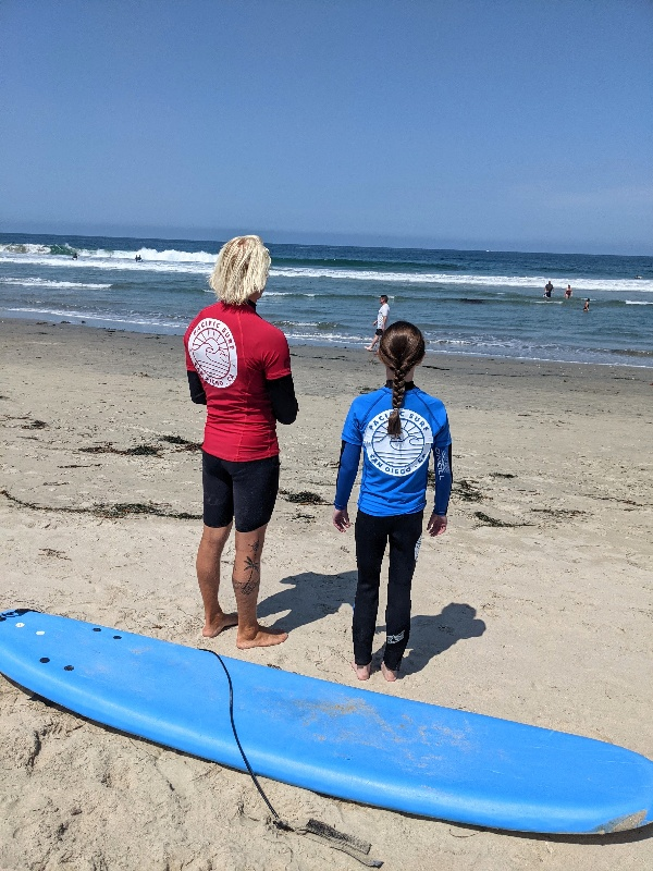 Pacific Surf School instructor looks out over the water with a student by his side.