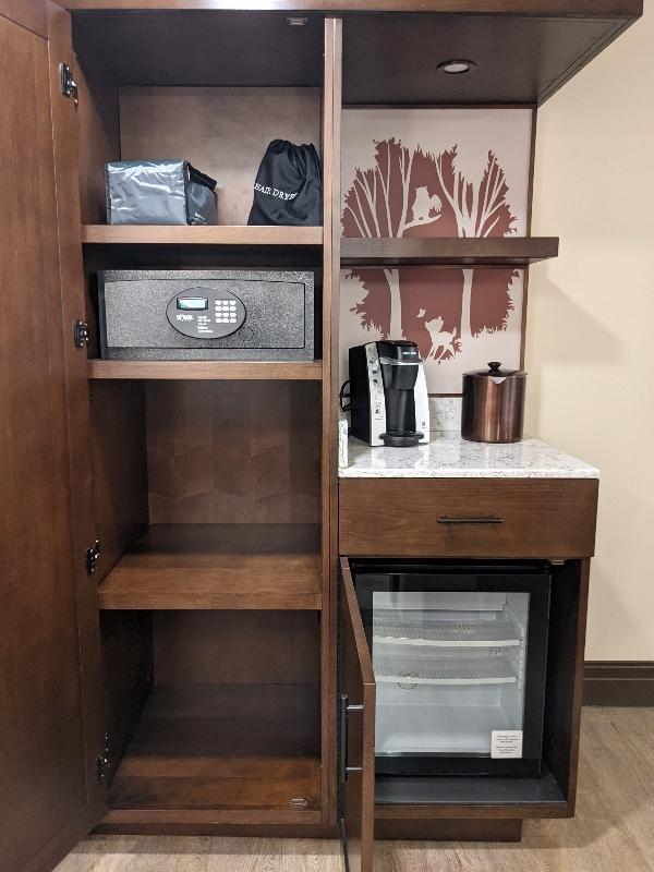 Shelves, a mini fridge, Keurig coffee maker, and in room safe at Disney's Wilderness Lodge
