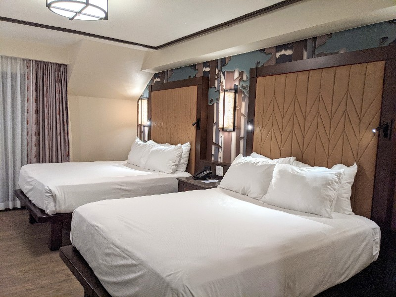 Two queen beds with stylized tree design behind the headboards.