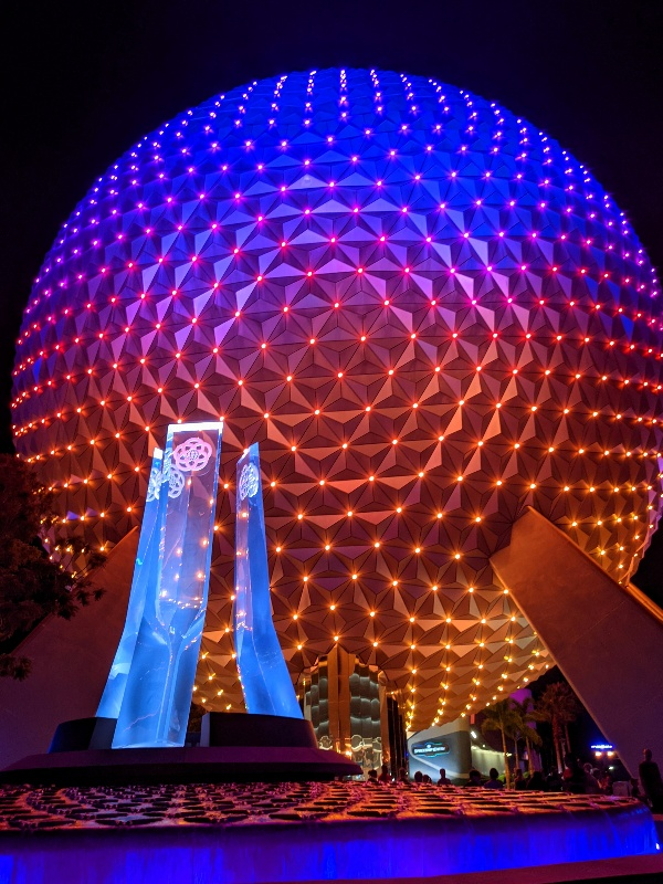 Epcot's Spaceship Earth covered in shades of blue, pink, red, and orange with points of light on every facet.