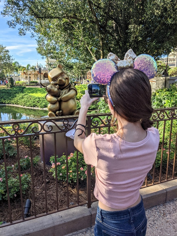 Girl takes photo of Winnie the Pooh and Piglet Fab 50 statue with Main Street in the background at Magic Kingdom