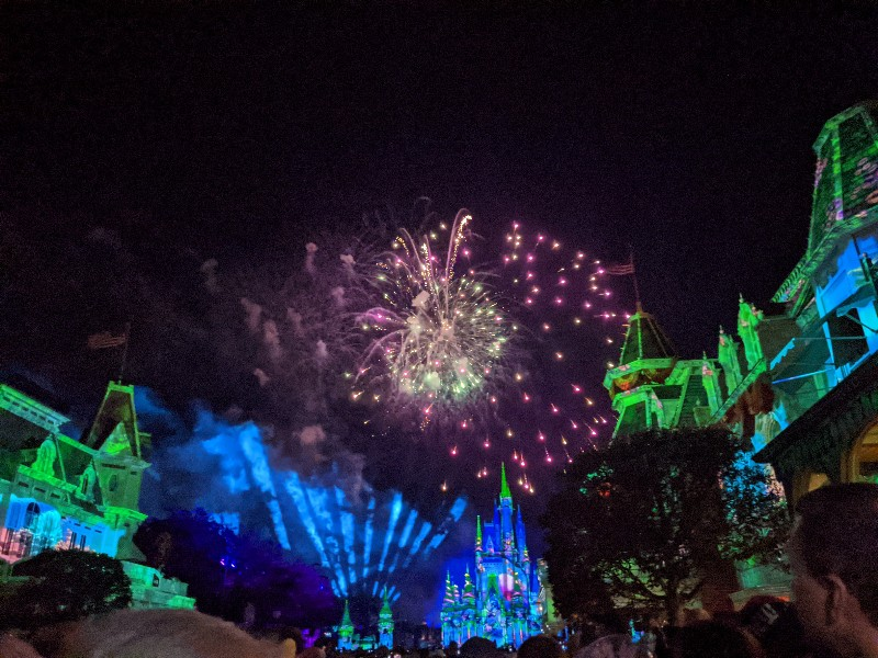Fireworks glitter over a colorful Cinderella Castle as projections cover Main Street at Magic Kingdom