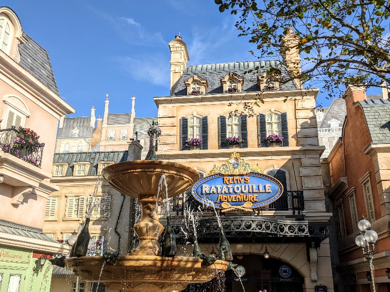 A fountain with sparkling water in front of the Remy's Ratatouille Adventure ride entrance